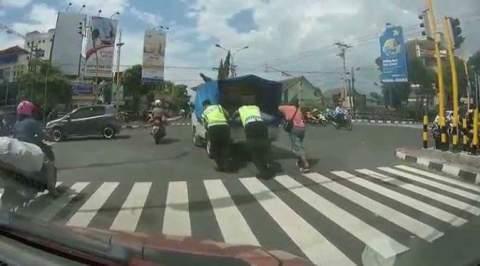 Polisi dorong mobil mogok di perempatan jalan