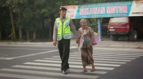 Polisi membantu menyebrangkan jalan