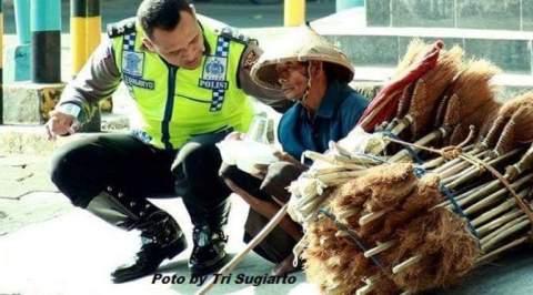 Polisi membantu tukang sapu