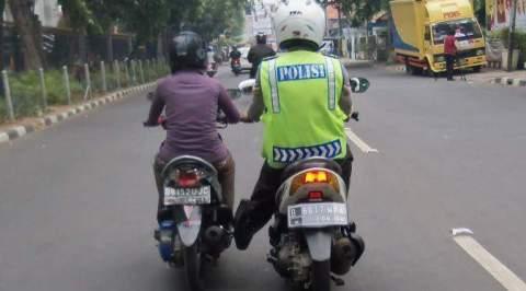 Polisi mendorong motor yang sedang mogok